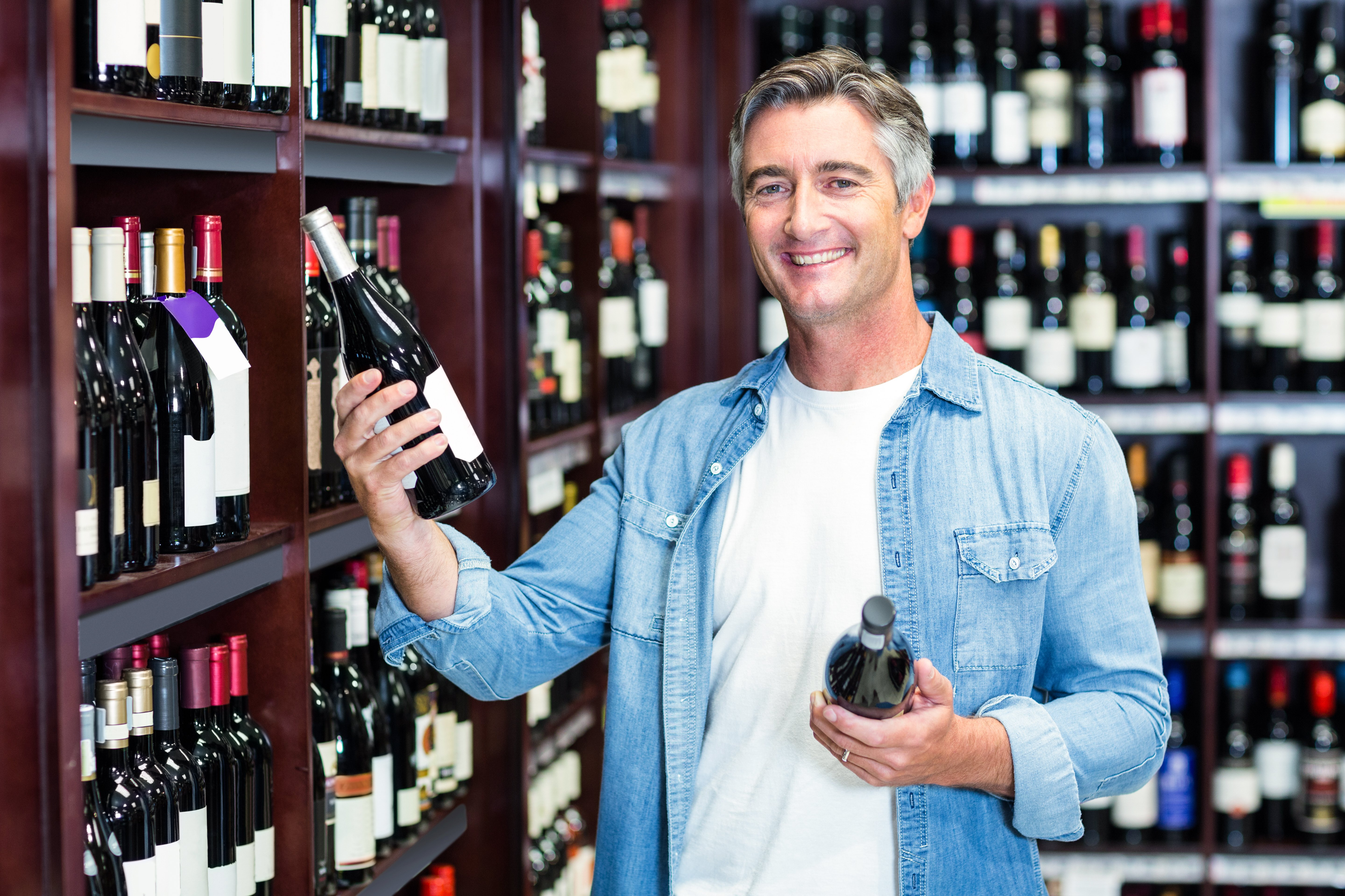 Smiling man holding bottles of wine in supermarket
